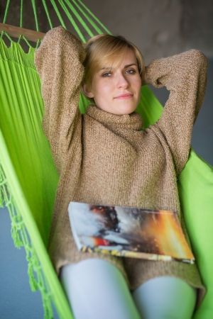 Beautiful woman rest with magazine in hammock photo