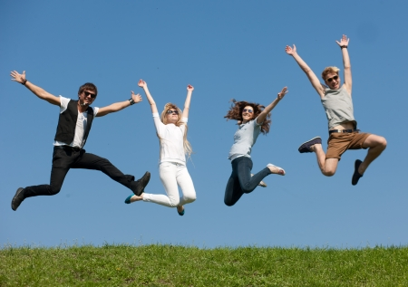 Group of young people jump across blue sky 스톡 콘텐츠