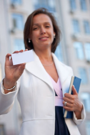 Beautiful businesswoman with visit card across office Stock Photo - 19062966