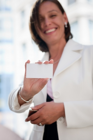 Beautiful businesswoman with visit card across office Stock Photo - 19062960