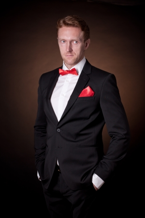 elegant man in a tuxedo with a red bow