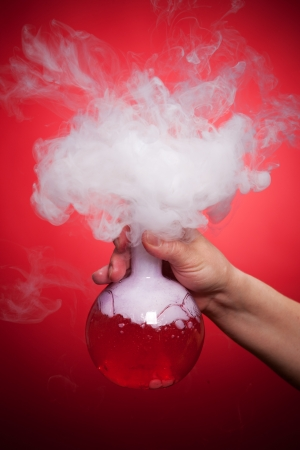 Steaming flask with red liquid in the hand on a red background photo