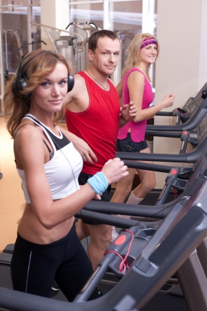 Group of people running on treadmill in gym photo