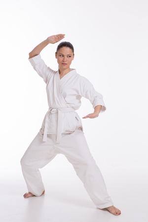 Mujer hermosa en la demostraci�n del ejercicio del arte mariscal kimono blanco photo