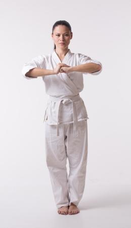 karate female: Woman in kimono going for greeting on white