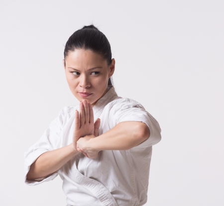 Woman in kimono show punch with elbow on white Stock Photo