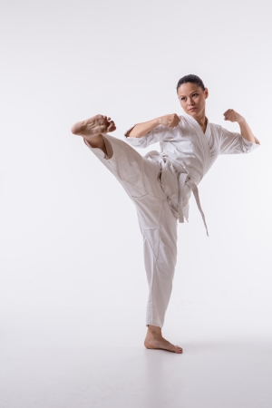 Beautiful woman in kimono show marshal art foot kick on white