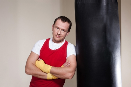 Man in yellow boxing gloves makes a series of exercises photo