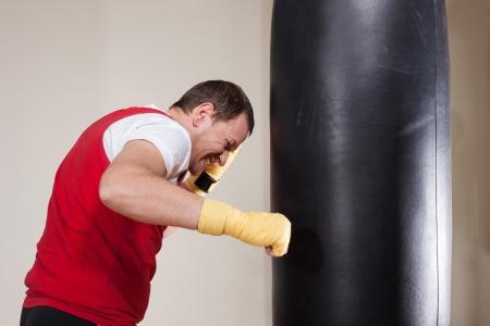 Man in boxing gloves punching bag in gym photo