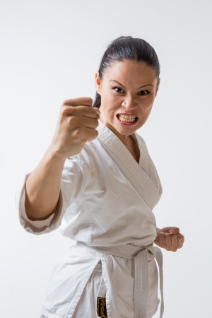 Funny woman in kimono show punch in martial art exercise Stock Photo