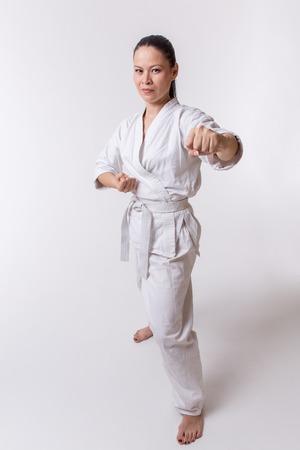 karateka: Funny woman in kimono show punch in martial art exercise on white
