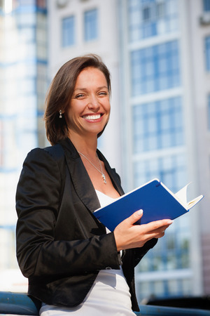 Portrait of beautiful business woman with diary photo