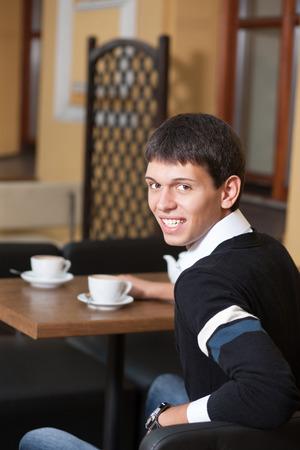 positiveness: Positividad en su sangre. Hombre joven que presenta para la c�mara a trav�s de la mesa con la taza de caf� Foto de archivo
