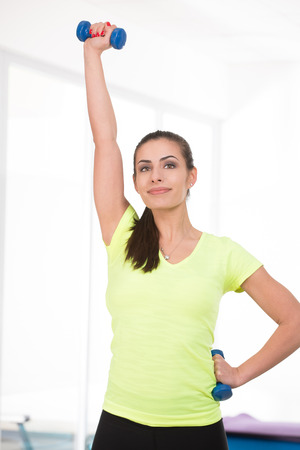 raise hand: Beautiful sporty woman raise hand with dumbbell in gym Stock Photo