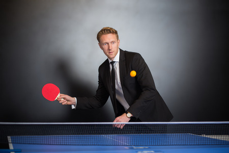 opponent: Businessman play tennis with opponent for relax  in office across  black wall with window. Stock Photo