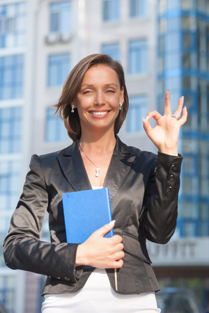 She is Okay and she show that. Portrait of beautiful businesswoman with Okay gesture photo