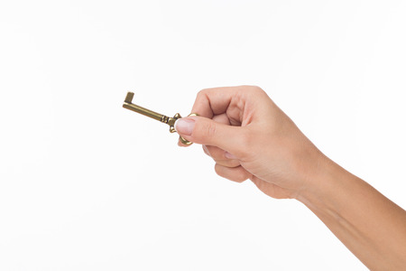 Raedy to open a door. Hand hold old key isolated on white photo