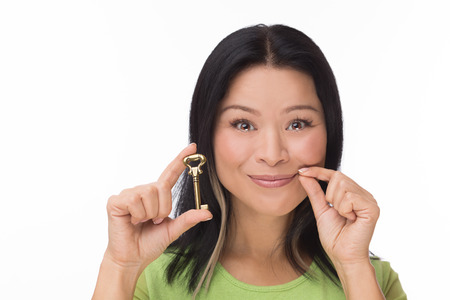shushing: Asian woman keep mouth locked with key isolated on white