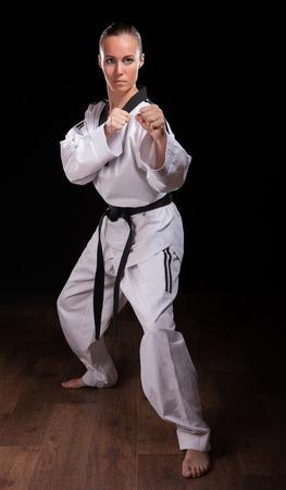 artes marciales: Ella es artes marciales m aster. Mujer en kimono espectáculo posición de defensa en fondo oscuro