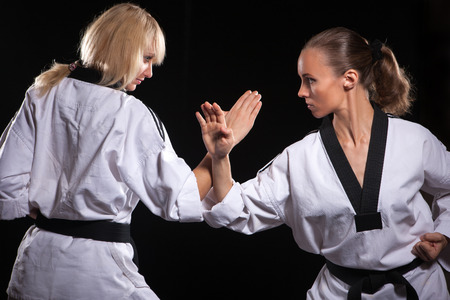 girl kick: Two fighters in white kimonos ready to start. Stock Photo