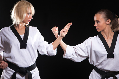 Girls ready to fight,  because they taekwondo masters. Two wemen stay in positions on black background
