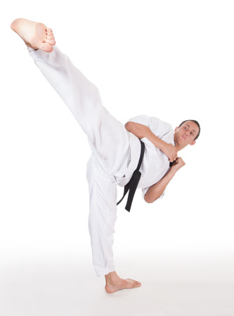 kata: He is fighter. Young man show foot kick in head on white.