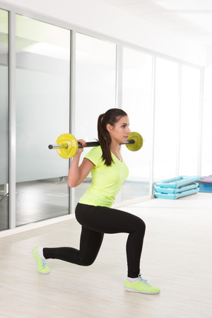 Sporty woman in gym in yellow t-shirt and black jogging bottoms