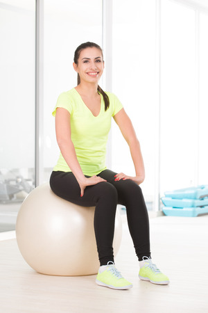 bottoms: Sporty woman in gym in yellow t-shirt and black jogging bottoms