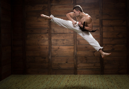 asian art: He strong and jumpy. Fighter jumping with foot kick in dojo