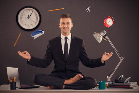 彼は、彼の仕事をしているオフィスでは、リラックスできる実業家です。ハンサムな実業家は、蓮華座のオフィスのテーブルの上に座るし、リラッ
