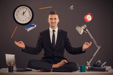 man exercise: He is businessman that can relax in office, while his work is doing. Handsome businessman sit on table in office in lotus position and try to relax. Stock Photo