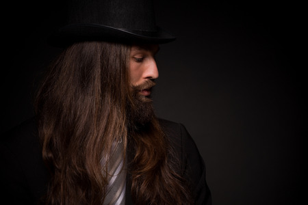 topper: He is a rock star and he can play guitar. Hipster with long hair and beard, weared in topper and black suit on dark background Stock Photo