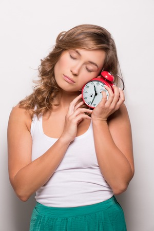 white singlet: Portrait of sleeping student after lessons. Girl in white singlet standing with alarm clock. Stock Photo