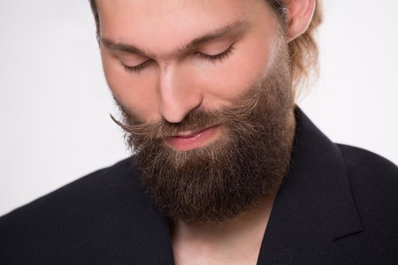 Young bearded model with moustache smiling. Man in black suit in photostudio. Reklamní fotografie