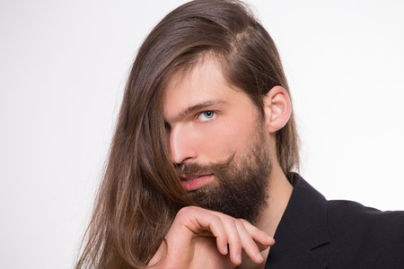 trendy male: Well-groomed man posing.  Metrosexual with beautiful long hair and moustache looking serious. Stock Photo