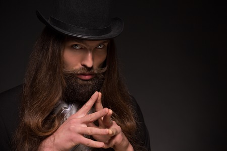 Serious long-haired magician thinking about hypnosis. Man with moustache having gimlet eyes.