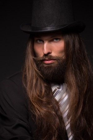 misterious: Portrait of handsome magician performing black magic. Man with long hair and top hat isolated on dark background.