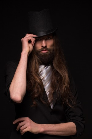 magician: Magician with moustache touching histop hat. Long-haired man in black suit isolated on dark background.