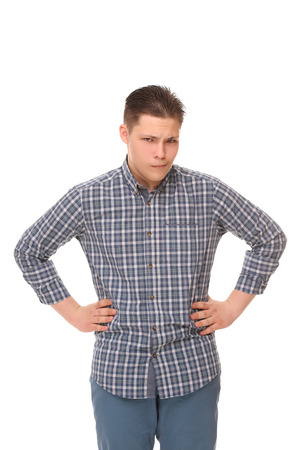 blue plaid: Serious teenager with his arms akimbo. Boy in blue plaid shirt and jeans posing on white. Stock Photo