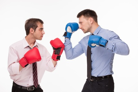 Business battle betweent two men. Men in red- and blue-coloured boxing gloves competing about business strategy.