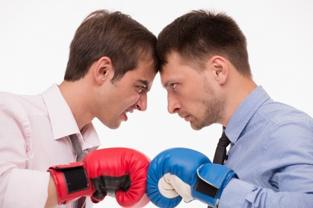 competitiveness: Competitiveness between two real business monsters. Men in boxing gloves hating each other. Stock Photo