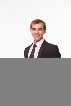 friendliness: Young successful businessman smiling. Man in business suit possessing friendliness towards the employees. Stock Photo