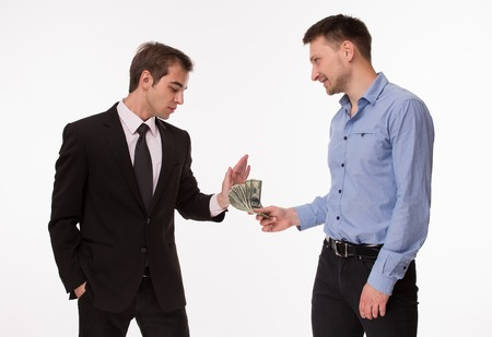 corruptible: Businessman in dark-coloured business suit rejecting money from man in blue-coloured shirt. Two men posing on white.