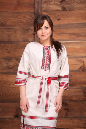 thick hair: Pretty Ukrainian girl dressed in traditional costume embellished with embroideries. Woman with dark thick hair isolated on wooden background. Stock Photo