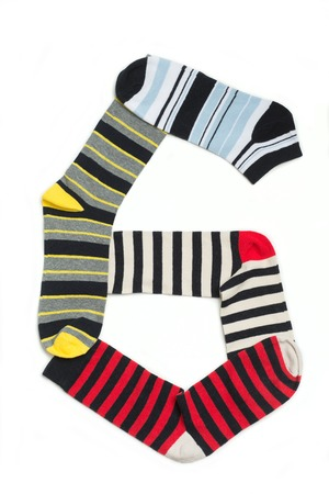 white socks: Number six made from socks in lines. Socks with different colours isolated on white. Stock Photo