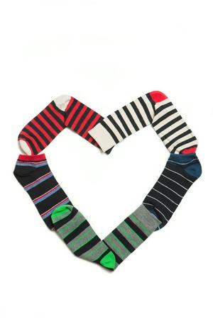 white socks: Beautiful heart made from many-coloured socks. Many socks organized on white backgroung.