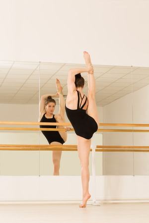 ballerina costume: Picture of ballerina in studio. Slim and slender girl standing in front of mirror and training.
