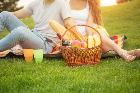 Young couple having picnic in the park. Man and woman came with basket full of food and drinks.