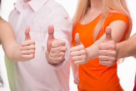 no problems: Four thumbs meaning no problems any more. Young people showing thumbs up isolated on white background. Stock Photo