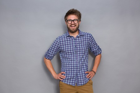 arms akimbo: Portrait of smiling young man in glasses on grey background. Man in flowing navy blue plaid shirt posing with his arms akimbo.